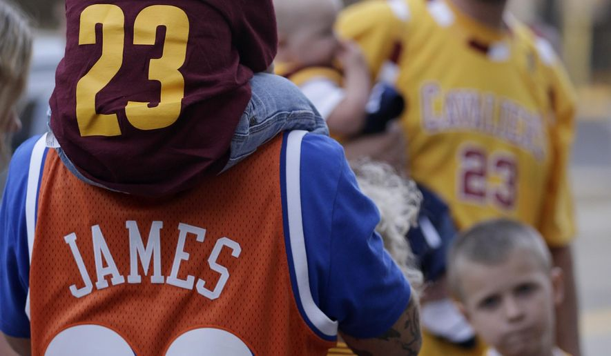 Cleveland Cavaliers fans wear the #23 jersey as they wait in line to enter the arena  before the Cavaliers play an NBA scrimmage basketball game Wednesday, Oct. 1, 2014, in Cleveland. (AP Photo/Tony Dejak)