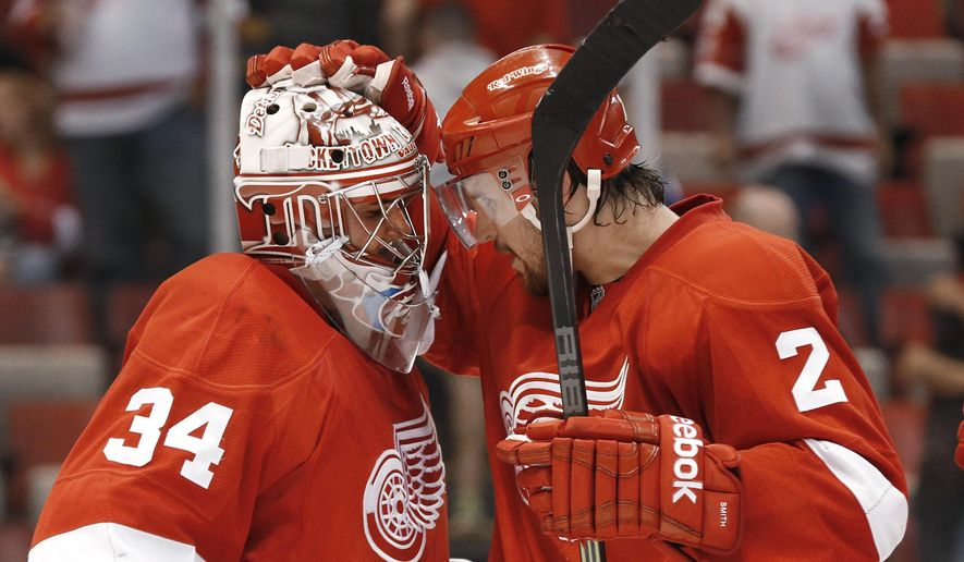 Detroit Red Wings goalie Petr Mrazek (34) celebrates their 3-0 win against the Toronto Maple Leafs with Brendan Smith (2) after a preseason NHL hockey game in Detroit Monday, Sept. 29, 2014. (AP Photo/Paul Sancya)
