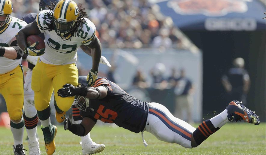 Green Bay Packers running back Eddie Lacy (27) tries to avoid a tackle by Chicago Bears linebacker Lance Briggs (55) in the first half of an NFL football game Sunday, Sept. 28, 2014, in Chicago. (AP Photo/Nam Y. Huh)