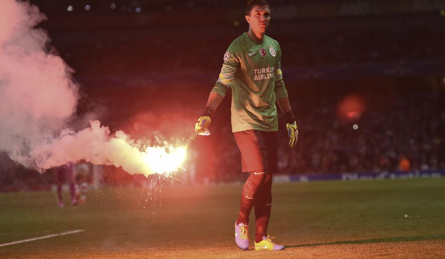 Galatasaray's goalkeeper Fernando Muslera carries a flare during the Champions League Group D soccer match between Arsenal  and Galatasaray , at the Emirates Stadium in London, on Wednesday, Oct 1, 2014. (AP Photo/ Tim Ireland)