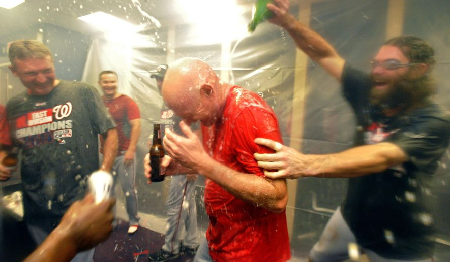 FILE - In this Sept. 16, 2014 file photo, Washington Nationals manager Matt Williams, center, is doused with champagne by Jayson Werth, right, as they celebrate their NL East division win after a baseball game against the Atlanta Braves in Atlanta. Williams was in his 18th game as a major league manager, still learning on the job with the Washington Nationals, when he went with his gut. Williams saw Bryce Harper hit a comebacker, jog out of the batter's box and veer off toward the dugout several strides before reaching first base. Williams, seething, yanked Harper from the lineup. That decision in April was one of thousands on the way to an NL East title as a rookie skipper that made clear, if there were any doubts, the 48-year-old Williams would do things his way.  (AP Photo/David Tulis, File)
