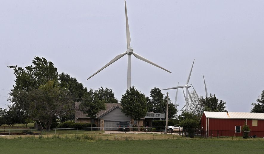In this July 28, 2014 photo, the home of Tammy and Rick Huffstutlar is surrounded by wind turbines in Calumet, Okla. A decade ago, states offered wind-energy developers an open-armed embrace, envisioning a bright future for an industry that would offer cheap electricity, new jobs and steady income for large landowners. Today, many of the same political leaders who initially welcomed the wind industry want to regulate it more tightly.   (AP Photo/Sue Ogrocki)