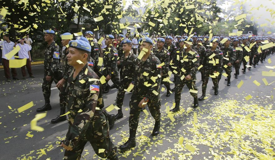 Confetti rains on marching Filipino UN peacekeepers as they are given a heroes welcome Wednesday, Oct. 1, 2014 at Camp Aguinaldo in suburban Quezon city northeast of Manila, Philippines. In a separate ceremony at the Presidential Palace earlier, Philippine President Benigno Aquino III said his government will no longer deploy troops to security hotspots in the world where they can face unclear or impossible U.N. peacekeeping missions like in the Golan Heights, where Filipino forces came under attack by al-Qaida-linked insurgents. Aquino III said Wednesday hundreds of Filipino peacekeepers were tasked to guard a buffer zone separating Israel and Syria. But when the current Syrian conflict spilled over into the buffer zone and anti-government Islamic militants started attacking the Filipino peacekeepers, their mission became unclear.  (AP Photo/Bullit Marquez)