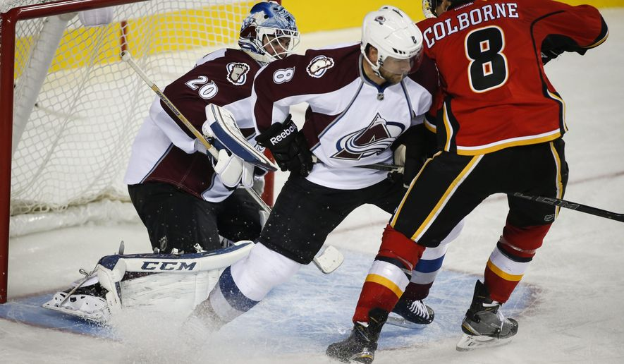 Colorado Avalanche's Jan Hejda, center, from the Czech Republic, keeps Calgary Flames' Joe Colborne, right, away from goalie Reto Berra during third period NHL pre-season hockey action in Calgary,  Alberta, Tuesday, Sept. 30, 2014.(AP Photo/The Canadian Press, Jeff McIntosh)
