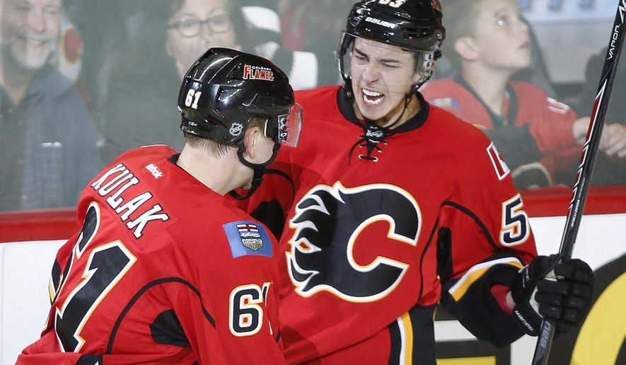 Calgary Flames' Johnny Gaudreau, right, celebrates his goal with teammate Brett Kulak during second period NHL pre-season hockey action against the Colorado Avalanche in Calgary,  Alberta, Tuesday, Sept. 30, 2014.(AP Photo/The Canadian Press, Jeff McIntosh)