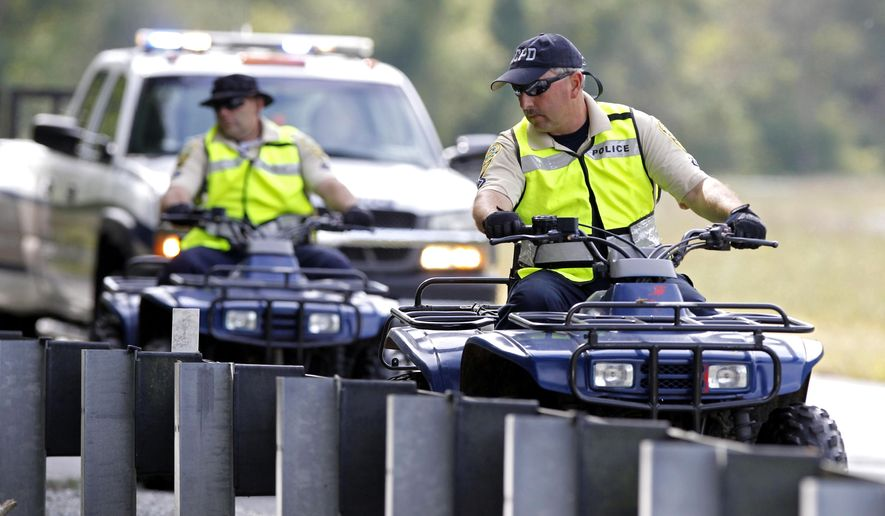 Albemarle County Police riding all-terrain vehicles perform a search along the edge of Monacan Trail Road on Sunday, Sept. 28, 2014. Hannah Elizabeth Graham, 18, a second-year University of Virginia student, went missing Sept. 13. (AP Photo/The Daily Progress, Ryan M. Kelly)