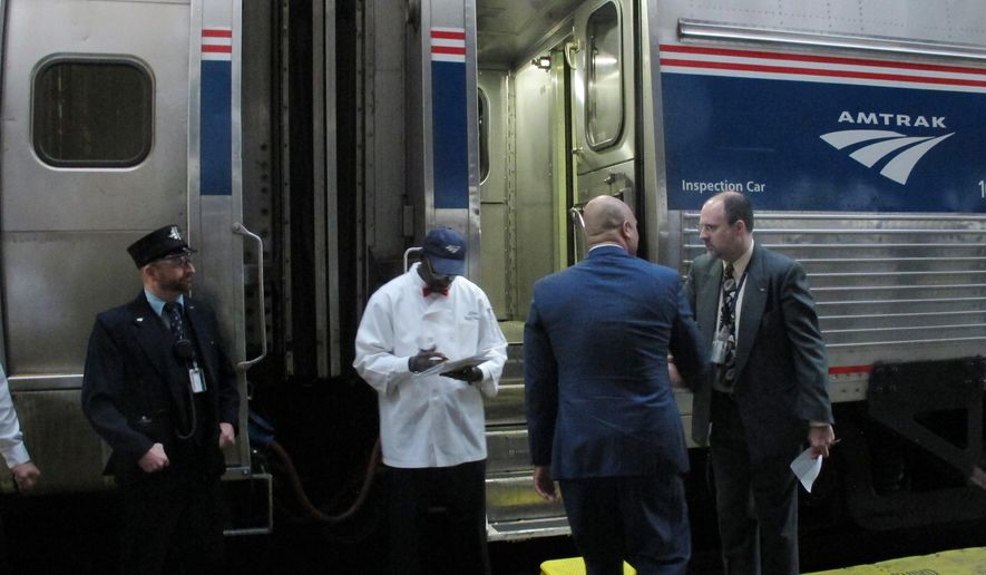 Democratic U.S. Rep. Andre Carson, second from right,boards an Amtrak train at Union Station in Indianapolis on Wednesday, Oct. 1, 2014, following Amtrak CEO Joe Boardman's announcement that the passenger train service will add free Wi-Fi, modest food service and business-class seating to the Hoosier State passenger line that runs four days a week between Indianapolis and Chicago. The line lost its federal funding last year under legislation Congress passed in 2008. Indiana is negotiating with a private vendor that wants to operate the line. (AP Photo/Rick Callahan)