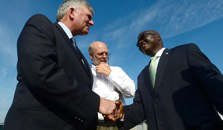 Franklin Graham, left, shakes hands with Liberian Ambassador to the U.S., Jeremiah C. Sulunteh Wednesday, Oct. 1, 2014, in Charlotte, N.C. The Christian relief agency Samaritan's Purse, headed by Graham, is airlifting tons of protective equipment and supplies to Ebola-stricken Liberia. (AP Photo/The Charlotte Observer, Todd Sumlin) MAGS OUT; TV OUT; NEWSPAPER INTERNET ONLY