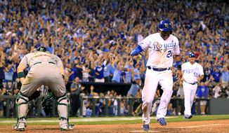 Kansas City Royals' Christian Colon scores the game-winning run past Oakland Athletics catcher Derek Norris during the 12th inning of the AL wild-card playoff baseball game Tuesday, Sept. 30, 2014, in Kansas City, Mo. The Royals won 9-8. (AP Photo/Jeff Roberson)