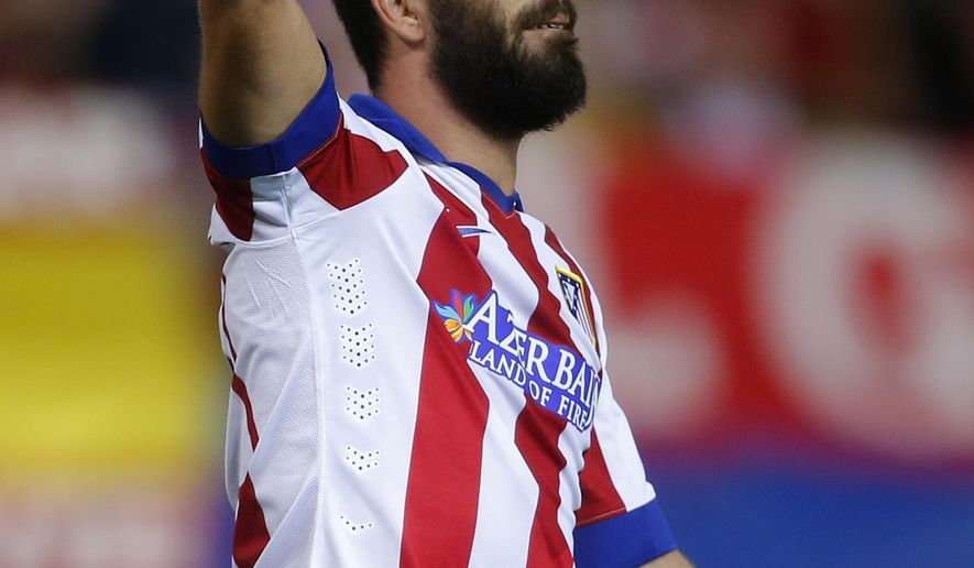 Atletico's Arda Turan celebrates after scoring during the Group A Champions League soccer match between Atletico de Madrid and Juventus at the Vicente Calderon stadium in Madrid, Spain, Wednesday Oct. 1, 2014. (AP Photo/Andres Kudacki)