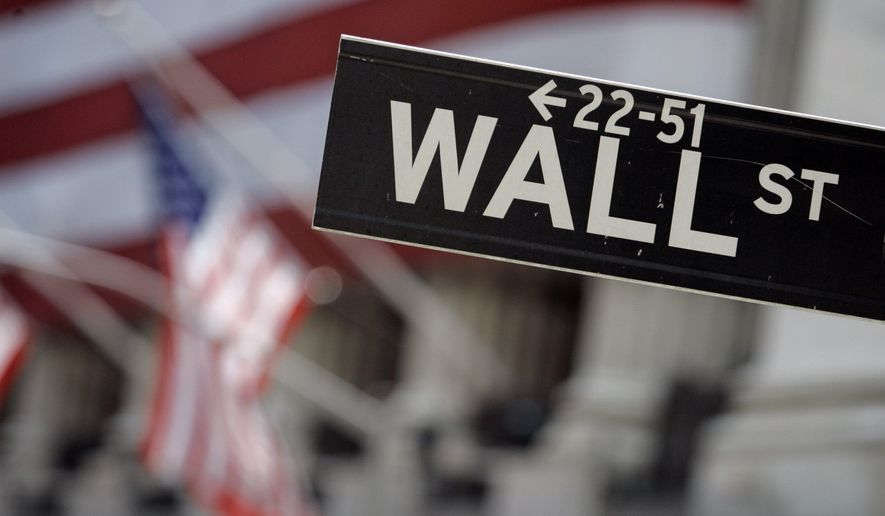 A Wall Street sign is mounted near the flag-draped facade of the New York Stock Exchange in this May 11, 2007, file photo. (AP Photo/Richard Drew, File)