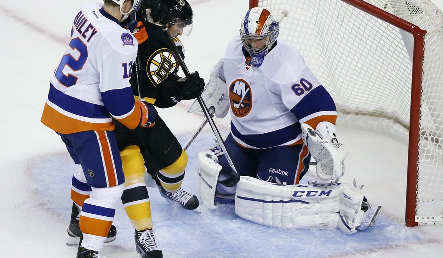 New York Islanders left wing Josh Bailey (12) prevents Boston Bruins left wing Loui Eriksson from getting to the puck in the crease as Islanders goalie Kevin Poulin (60) protects the net during the third period of an NHL preseason hockey game in Boston, Tuesday, Sept. 30, 2014. The Islanders won 5-3. (AP Photo/Elise Amendola)