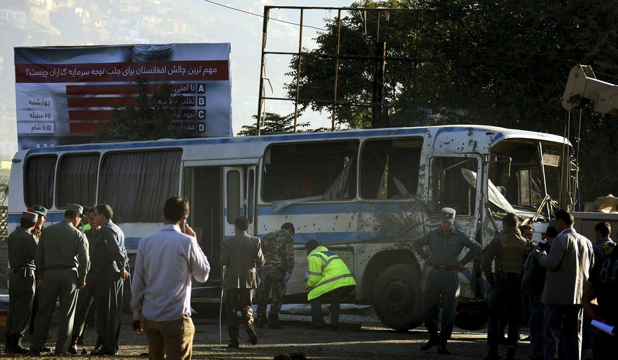 Afghan security forces walk around a destroyed army bus following a suicide attack in Kabul, Afghanistan, Wednesday, Oct. 1, 2014. Two suicide bombers in the Afghan capital targeted two buses carrying Afghan army troops on Wednesday, killing several people and wounding over a dozen others, police said.  (AP Photo)