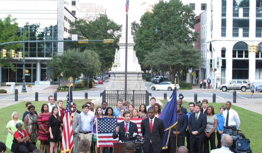 Democratic candidate for governor in South Carolina Vincent Sheheen, left, and Democratic lieutenant governor candidate Bakari Sellers, right, talk about their proposal to take the Confederate flag down from a pole in front of the Statehouse and replace it with an American flag on Wednesday, Oct. 1, 2014, in Columbia, S.C. A compromise in 2000 moved the Confederate flag from atop the Statehouse dome to its current location. (AP Photo/Jeffrey Collins)
