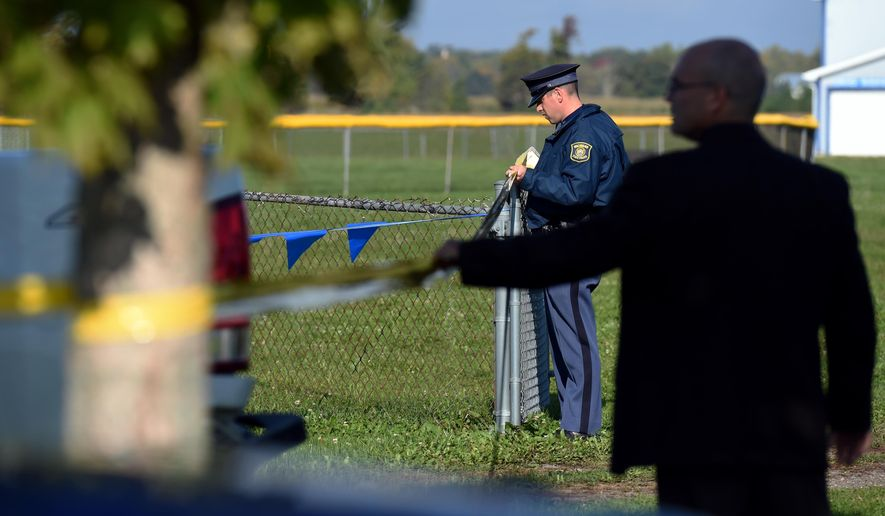 Michigan State Police trooper Pat Herman secures police tape to a fence at the entrance to Lincoln High School's football field on Wednesday morning, Oct. 1, 2014, in Ypsilanti, Mich. A 13-year-old boy was electrocuted at a middle school football game the night before when he was shocked while leaning against a metal ramp to the bleachers. The boy was taken to a hospital for treatment, where he was listed in critical condition.  (AP Photo/The Ann Arbor News, Melanie Maxwell)