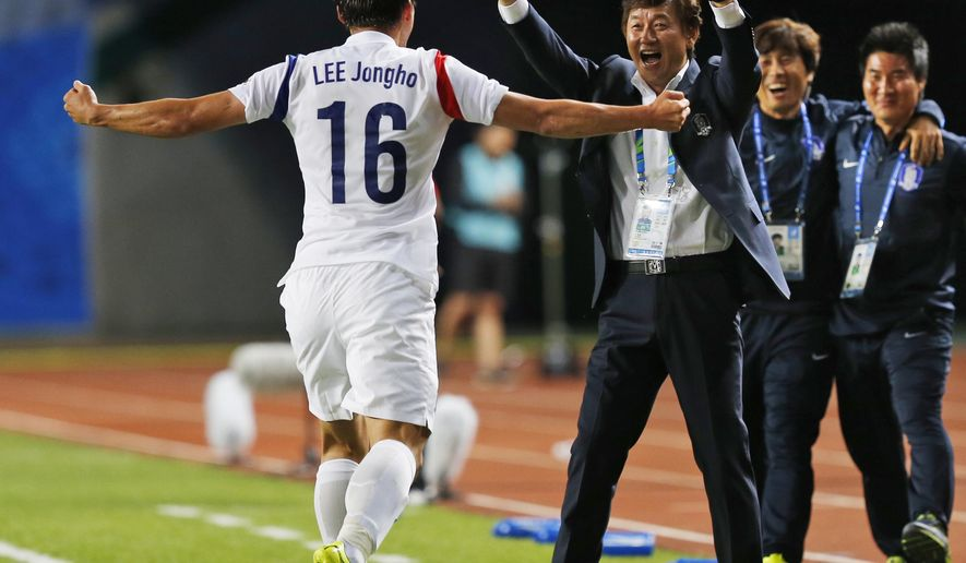 South Korea's Lee Jongho, left, celebrates with his coach after scored a goal during the men's football semifinal against Thailandat the 17th Asian Games in Incheon, South Korea, Tuesday, Sept. 30, 2014.  (AP Photo/Kin Cheung)