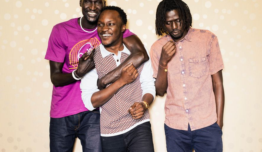"""In this Monday, Sept. 29, 2014 photo, Ger Duany, Arnold Oceng, and Emmanuel Jal pose for a portrait during press day for """"The Good Lie"""" at Le Montrose Hotel in Los Angeles. In the film, Jal portrays Paul, the quick-learning adult member of a surviving trio of adopted brothers who are relocated to Kansas City, separated from their sister who was dispatched to Boston. He's joined on screen by fellow former Sudanese refuge Duany and British actor Oceng, who plays the group's de-facto chief tasked with reuniting the family in America.  (Photo by Casey Curry/Invision/AP)"""