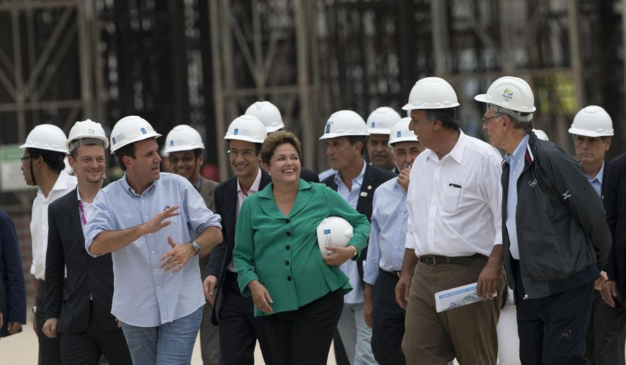 Rio Mayor Eduardo Paes, 3rd left with blue shirt, Brazil's President Dilma Rousseff, center, Rio Governor Luiz Fernando Pezao, 2nd right, and President of Rio 2016, Carlos Nuzman, right whith jacket, visit the works of the Rio 2016 Olympic Park in Rio de Janeiro, Brazil, Tuesday, Sept. 30, 2014. Chaired by Nawal El Moutawakel, the IOC Coordination Commission makes its seventh visit to Rio de Janeiro to monitor the preparation of the city for the 2016 Olympic and Paralympic Games. (AP Photo/Silvia Izquierdo)