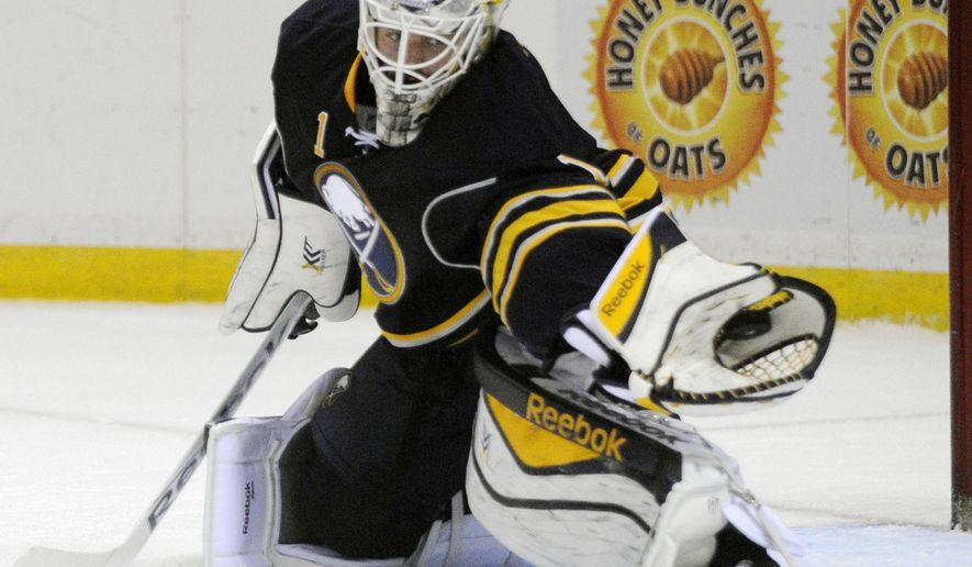 Buffalo Sabres goaltender Jhonas Enroth, of Sweden, reaches out to make a glove save against the Washington Capitals during the second period of an NHL hockey preseason game, Wednesday, Oct., 1, 2014, in Buffalo, N.Y. (AP Photo/Gary Wiepert)