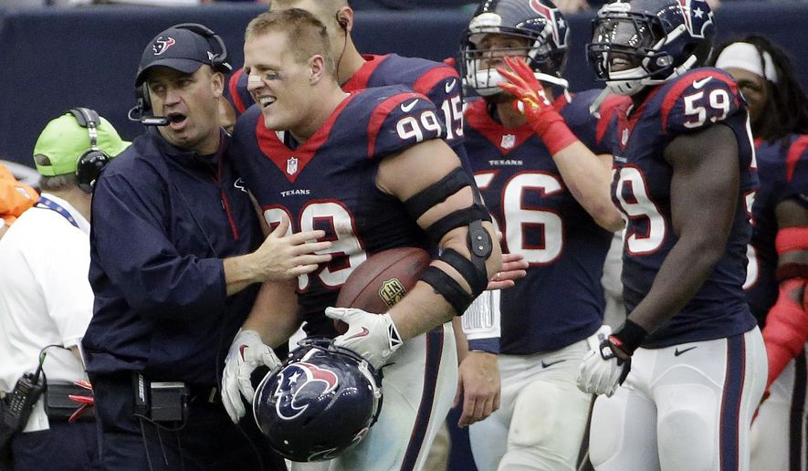Houston Texans' J.J. Watt (99) celebrates with Texans head coach Bill O'Brien after he returned an interception 80 yards for a touchdown against the Buffalo Bills during the third quarter of an NFL football game, Sunday, Sept. 28, 2014, in Houston. (AP Photo/David J. Phillip)