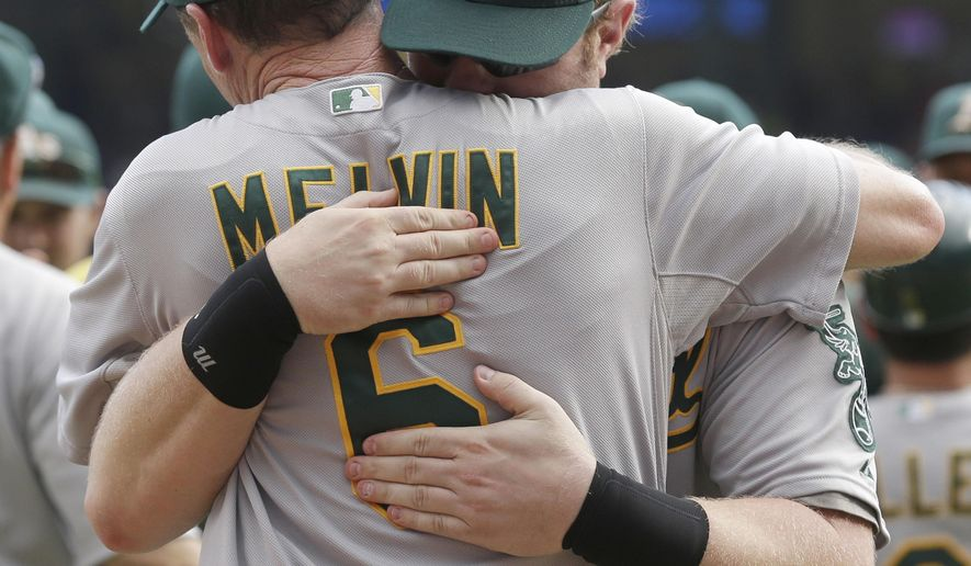Oakland Athletics manager Bob Melvin (6) is hugged by designated hitter Adam Dunn after a baseball game against the Texas Rangers in Arlington, Texas, Sunday, Sept. 28, 2014. The Athletics won 4-0, clinching a playoff spot. (AP Photo/LM Otero)