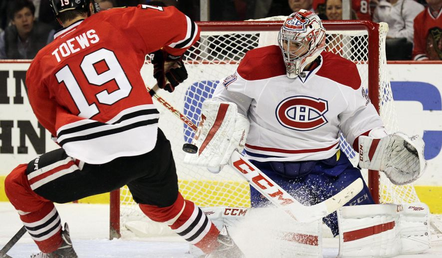 Montreal Canadiens goalie Carey Price (31), right, blocks a shot by Chicago Blackhawks center Jonathan Toews (19) during the second period of a preseason NHL hockey game in Chicago, Wednesday, Oct. 1, 2014. (AP Photo/Nam Y. Huh)