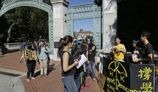 University of California at Berkeley students pass out yellow ribbons and educate others  in support for the Umbrella Revolution, a group seeking democracy in Hong Kong, on Wednesday, Oct. 1, 2014, at Sather Gate in Berkeley, Calif. Student leaders of Hong Kong's pro-democracy protests warned that if the territory's top official doesn't resign by Thursday they will step up their actions, including occupying several important government buildings. By raising the stakes in the standoff, the protesters are risking another round of confrontation with police, who are unlikely to allow government buildings to be stormed. It also puts pressure on the Chinese government, which so far has said little beyond declaring the protests illegal and backing Hong Kong Chief Executive Leung Chun-ying's attempts to end them. (AP Photo/Ben Margot) **FILE**