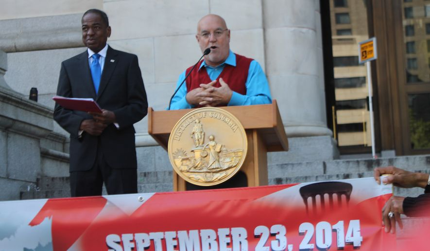 """Jose Sueiro, with the D.C. Hispanic Contractors Association, speaks at the """"Where's the $1 Billion"""" rally as D.C. Council member Vincent Orange looks on. Supporters say the D.C. government is giving short-shrift on contracts to small businesses. (Photo by Malcolm Barnes)"""