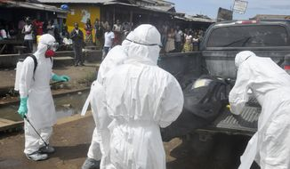 Health workers in protective gear load the body of a woman suspected of dying from the Ebola virus, into a pickup truck near the area of Freeport in Monrovia, Liberia, Wednesday, Oct. 1, 2014. The first case of Ebola diagnosed in the U.S. has been confirmed in a man who recently traveled from Liberia to Dallas. (AP Photo/Abbas Dulleh)