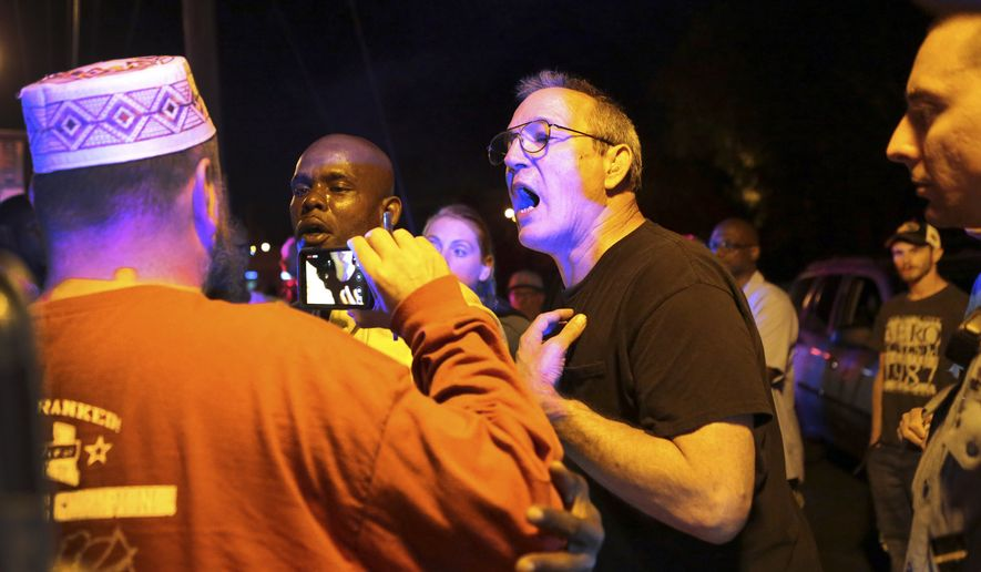 Larry Claffy, center, of Overland, and a patron of Faraci Pizza, in Ferguson, Mo., has words with Umar Lee outside the restaurant on Tuesday, Sept. 30, 2014. There has been unrest in the St. Louis suburb since the Aug. 9 shooting of Michael Brown, an unarmed, black 18-year-old, by a white police officer. (AP Photo/St. Louis Post-Dispatch, Robert Cohen)