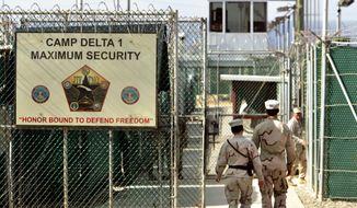 U.S. military guards walk within Camp Delta military-run prison, at the Guantanamo Bay U.S. Naval Base, Cuba, June 27, 2006. (Associated Press) ** FILE **