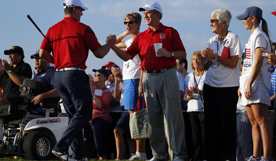 Retired Marine Cpl. Michael Meyer, left, shakes hands with former U.S. President George W. Bush after teeing off in the Bush Center Warrior Open golf tournament during an opening ceremony, Thursday, Oct. 2, 2014, at the Las Colinas Country Club in Irving, Texas. This is the fourth year for the 36-hole tournament featuring servicemen wounded in combat service. (AP Photo/The Dallas Morning News, Tom Fox)  MANDATORY CREDIT; MAGS OUT; TV OUT; INTERNET USE BY AP MEMBERS ONLY; NO SALES