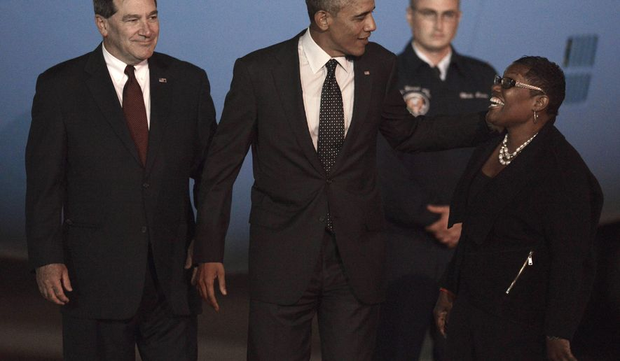 President Barack Obama center, jokes with Gary (Ind.) Mayor Karen Freeman-Wilson right, while Sen. Joe Donnely, D-Ind., left, watches after Obama arrived at the Gary/Chicago International Airport in Gary, Ind., Wednesday, Oct. 1, 2014. (AP Photo/Paul Beaty)