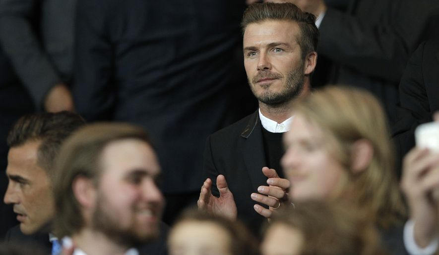 Former England and PSG soccer player David Beckham applauds as he takes his seat before the Champions League soccer match between PSG and Barcelona, at the Parc des Princes stadium, in Paris, Tuesday, Sept. 30, 2014. (AP Photo/Christophe Ena)