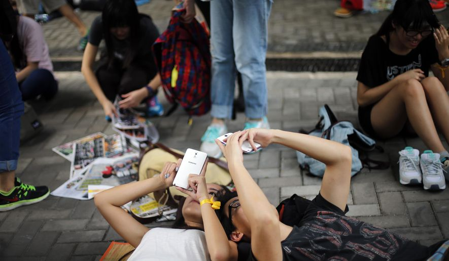 "Student pro-democracy activists surf on their smartphones while resting on the streets near the government headquarters, Thursday, Oct. 2, 2014 in Hong Kong.  China's ruling party mouthpiece warned of ""chaos"" and expressed strong support for Hong Kong's embattled leader in his face-off with pro-democracy protesters who have threatened to occupy government offices unless he steps down by the end of Thursday. (AP Photo/Wong Maye-E)"