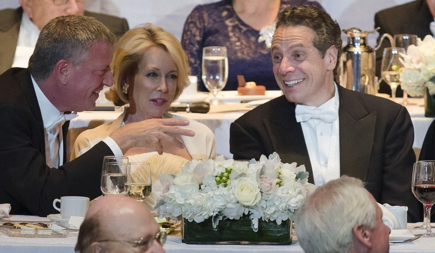 New York Gov. Andrew Cuomo, right, sits alongside New York Mayor Bill de Blasio, left, and Nan Smith, center, during the 69th Annual Alfred E. Smith Memorial Foundation Dinner, a charity gala organized by the Archdiocese of New York, at the Waldorf-Astoria hotel, Wednesday, Oct. 1, 2014, in New York. (AP Photo/John Minchillo)