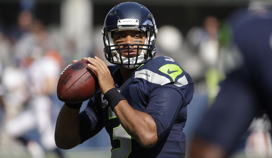 FILE - In this  Sunday, Sept. 21, 2014 file photo, Seattle Seahawks quarterback Russell Wilson passes during warmups before an NFL football game against the Denver Broncos in Seattle. Seattle Seahawks quarterback Russell Wilson is speaking out about domestic violence and about being a bully as a child in a column for Derek Jeter's new website. Wilson was announced as a senior editor for The Players' Tribune on Thursday morning, Oct. 2, 2014. (AP Photo/Elaine Thompson, File)