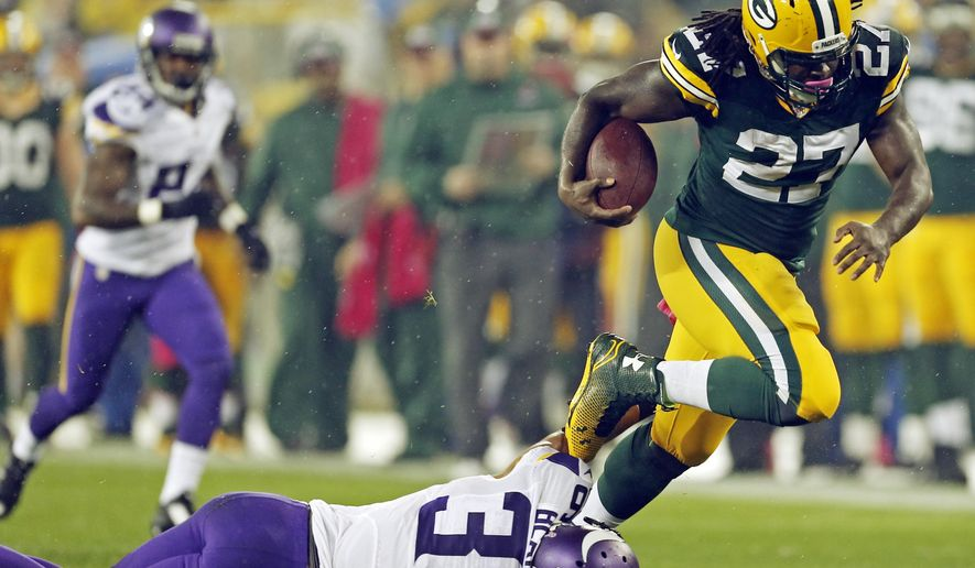 Green Bay Packers' Eddie Lacy runs past Minnesota Vikings' Robert Blanton during the first half of an NFL football game Thursday, Oct. 2, 2014, in Green Bay, Wis. (AP Photo/Mike Roemer)