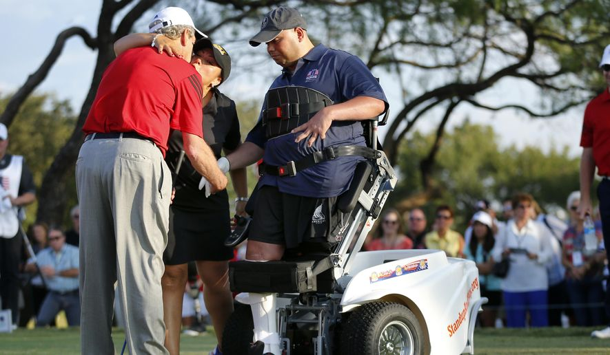 Claudia Avila, wife of injured vet Retired Army Capt. Luis Avila, right,  gives former U.S. President George W. Bush, left, a kiss after her husband made the ceremonial tee off in the Bush Center Warrior Open golf tournament during an opening ceremony, Thursday, Oct. 2, 2014, at the Las Colinas Country Club in Irving, Texas. This is the fourth year for the 36-hole tournament featuring servicemen wounded in combat service. (AP Photo/The Dallas Morning News, Tom Fox)  MANDATORY CREDIT; MAGS OUT; TV OUT; INTERNET USE BY AP MEMBERS ONLY; NO SALES