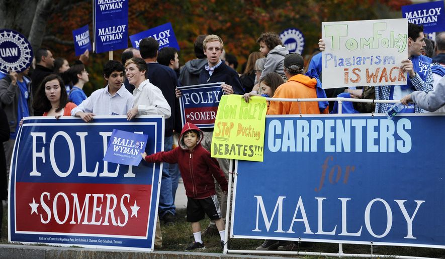 Gavan Jordan, center, 7, of Chaplin, Conn., holds a sign for incumbent Democrat Gov. Dannel P. Malloy, over a sign for Republican candidate for governor Tom Foley, before a debate between the two candidates at the University of Connecticut, Thursday, Oct. 2, 2014, in Storrs, Conn.  (AP Photo/Jessica Hill)