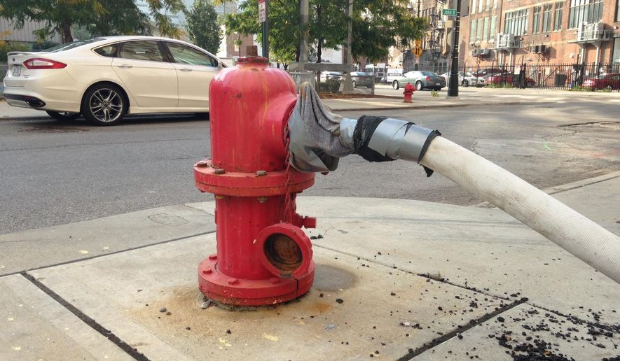 A makeshift water connection to a fire hydrant has been fashioned Thursday, Oct. 2, 2014 outside the 1515 Broadway coffeehouse in Detroit, Mich. A system of plastic pipe, garden hoses, duct tape and towels is providing water service to the coffeehouse and an adjoining jewelry store as city repairs to the water system serving the businesses are on hold, officials said.  (AP Photo/Mike Householder)