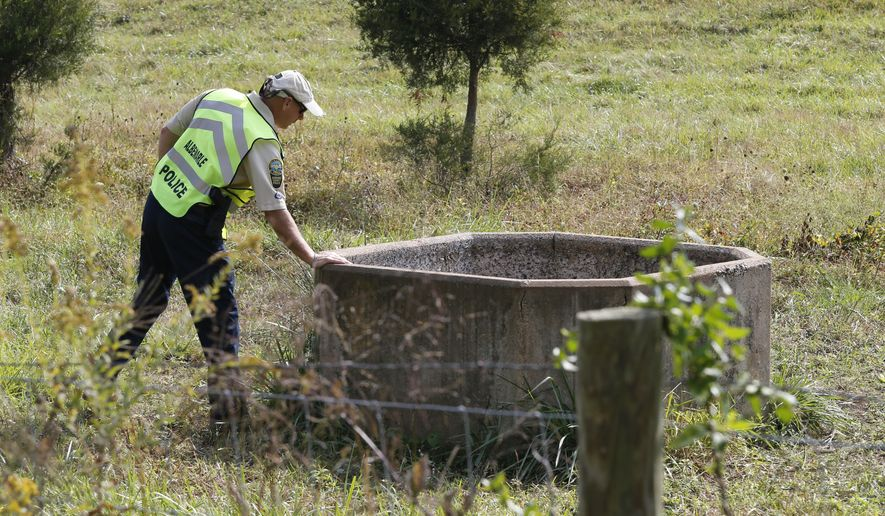 A police officer looks into a well while searching for missing University of Virginia student Hannah Graham in Keswick, Va., Thursday, Oct. 2, 2014.  Jesse Leroy Matthew Jr., charged with abducting Graham, didn't appear in court Thursday morning for a bond hearing on reckless driving charges.   (AP Photo/Steve Helber)