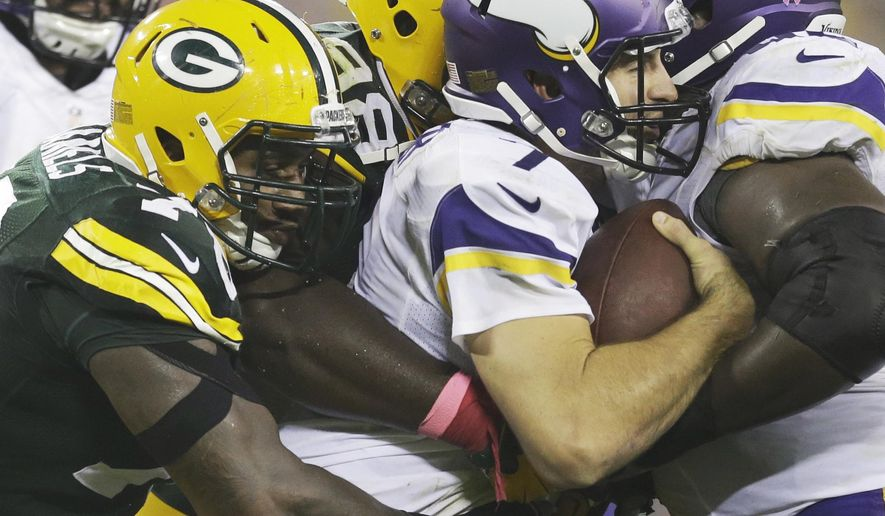 Green Bay Packers' Letroy Guion and Mike Daniels (76) sack Minnesota Vikings quarterback Christian Ponder during the first half of an NFL football game Thursday, Oct. 2, 2014, in Green Bay, Wis. (AP Photo/Tom Lynn)