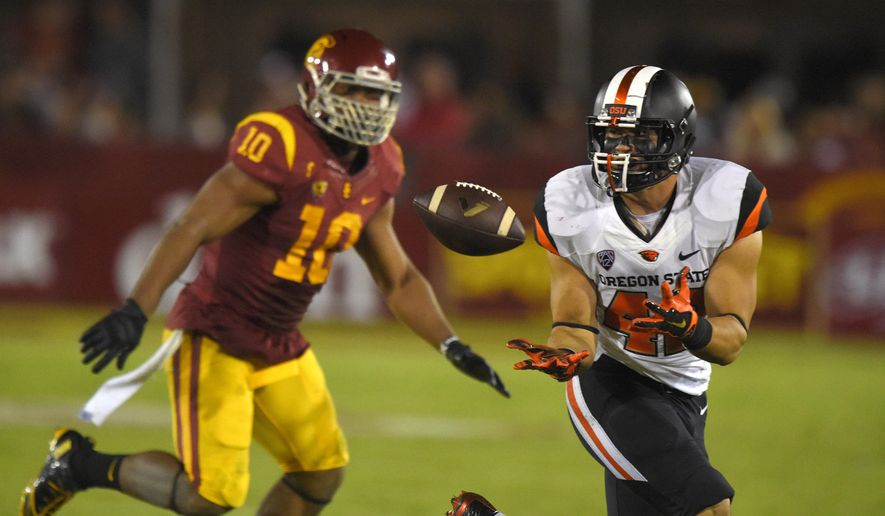 Oregon State fullback Ricky Ortiz, right, makes a catch as Southern California linebacker Hayes Pullard defends during the second half of an NCAA college football game, Saturday, Sept. 27, 2014, in Los Angeles.  USC won the game 35-10. (AP Photo/Mark J. Terrill)