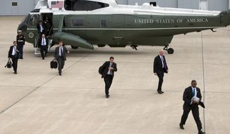 Secret Service agents arrive at Gary/Chicago International Airport ahead of the arrival of President Barack Obama, on Thursday, Oct. 2, 2014, in Gary, Ind. (AP Photo/Evan Vucci)