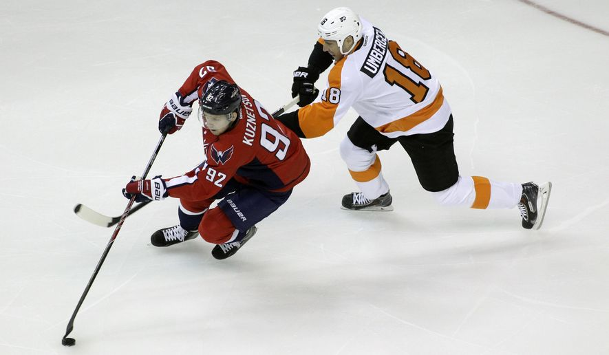 Washington Capitals' Evgeny Kuznetsov, of Russia, moves the puck as Philadelphia Flyers' R.J. Umberger defends during the first period of a preseason NHL hockey game, Thursday, Oct. 2, 2014, in Washington.(AP Photo/Luis M. Alvarez)