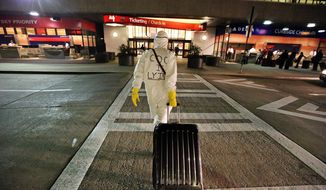 Two days after a man in Texas was diagnosed with Ebola, Dr. Gil Mobley, a Missouri doctor, walks to Hartsfield-Jackson Atlanta International Airport to check in and board a plane dressed in full protection gear Thursday morning, Oct. 2, 2014, in Atlantat. He was protesting what he called mismanagement of the crisis by the federal Centers for Disease Control and Prevention. (AP Photo/Atlanta Journal-Constitution, John Spink)