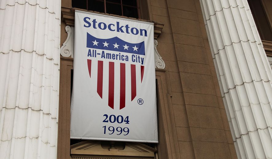 FILE - In this Feb. 29, 2012 file photo, a banner proclaiming Stockton as an All-America city hangs from city hall in Stockton, Calif.  A federal judge could rule Wednesday Oct. 1, 2014, on a bankruptcy exit plan for Stockton, an inland port city in California that in 2012 became the largest city in the U.S. to file for Chapter 9 protection before Detroit filed last year. U.S. Bankruptcy Judge Christopher Klein has scheduled a hearing in Sacramento in a trial that has lasted more than four months.(AP Photo/Ben Margot, File)