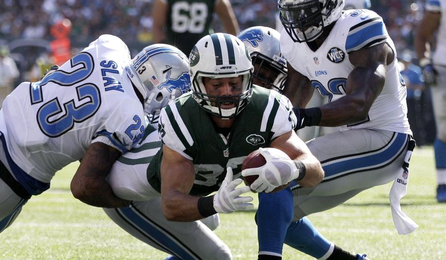 New York Jets wide receiver Eric Decker, center, dives between Detroit Lions cornerback Darius Slay, left, outside linebacker Tahir Whitehead, center right, and strong safety James Ihedigbo, right, for a touchdown during the second half of an NFL football game, Sunday, Sept. 28, 2014, in East Rutherford, N.J. (AP Photo/Frank Franklin II)