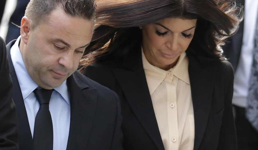 """The Real Housewives of New Jersey"" stars Giuseppe ""Joe"" Giudice, left, and his wife, Teresa Giudice, of Montville Township, N.J., walk toward Martin Luther King Jr. Courthouse before a court appearance, Thursday, Oct. 2, 2014, in Newark, N.J. The Giudices are scheduled to be sentenced on federal conspiracy and bankruptcy fraud charges. (AP Photo/Julio Cortez)"